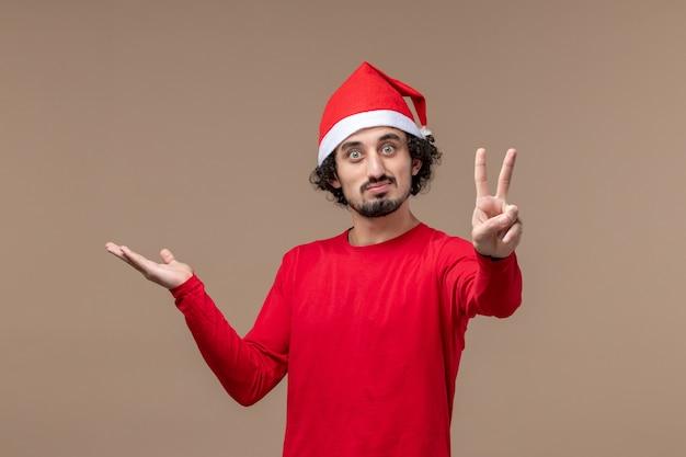 茶色の背景の休日の感情のクリスマスに穏やかな表情で正面図若い男
