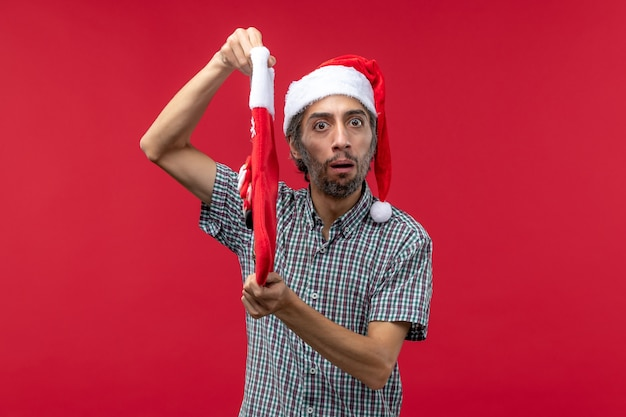 Front view of young man with christmas sock on red wall