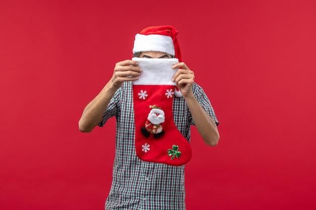 Vista frontale del giovane con il calzino di natale sulla parete rossa