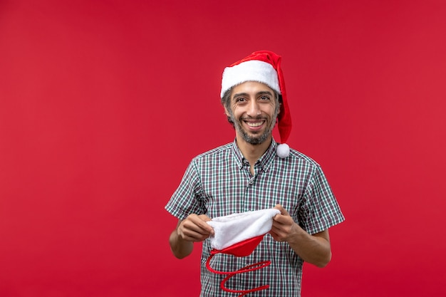 Front view of young man with christmas toy cap on the red wall