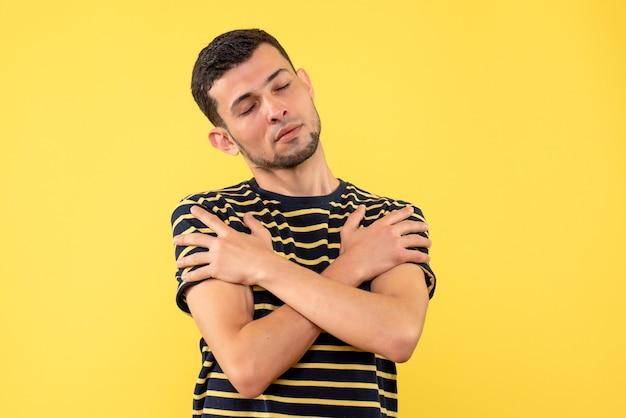노란색 격리 된 배경에 손을 건너 닫힌 된 눈을 가진 전면보기 젊은 남자