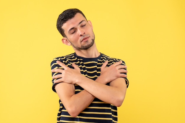 Front view young man with closed eyes crossing hands on yellow isolated background
