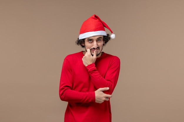 Front view young man with confused expression on brown background christmas emotion holiday