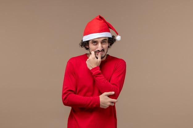 Вид спереди молодой человек с растерянным выражением лица на коричневом фоне рождественских эмоций