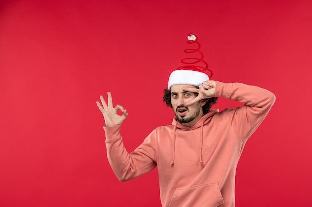 Vista frontale del giovane con espressione confusa sulla parete rossa