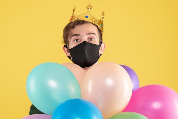 Вид спереди молодой человек с короной и черной маской, держащий воздушные шары на желтом