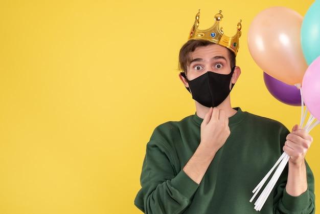 正面図黄色の風船を保持している王冠と黒のマスクを持つ若い男