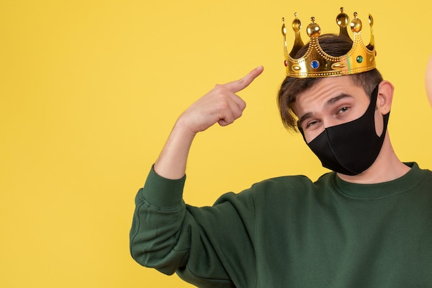 Front view young man with crown and black mask pointing at his crown on yellow