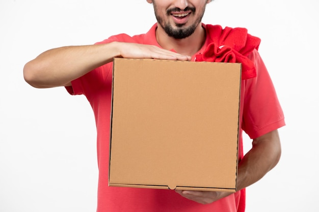 Front view of young man with delivery food box on a white wall