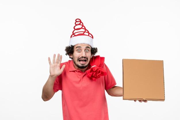 Vista frontale del giovane con la scatola del cibo di consegna sulla parete bianca