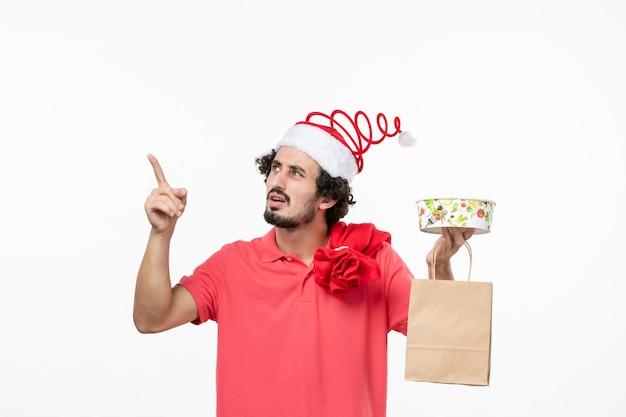 Vista frontale del giovane con cibo da consegna sul muro bianco