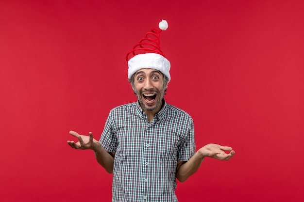 Front view of young man with excited expression on red wall