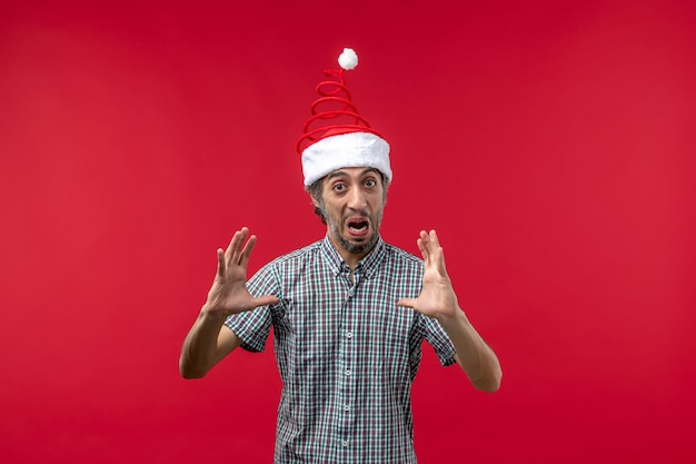 Front view of young man with excited expression on the red wall