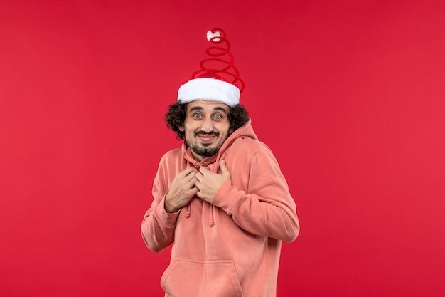 Vista frontale del giovane con espressione eccitata sulla parete rossa