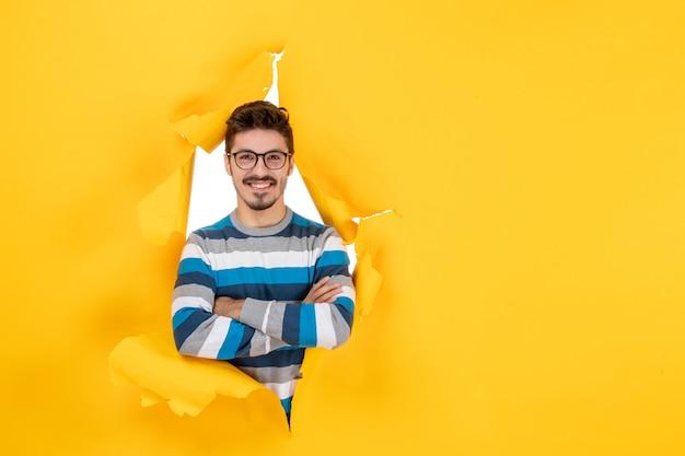 Вид спереди молодой человек в очках, глядя через рваную бумажную желтую стену