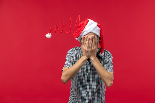 Front view of young man with funny toy cap on red wall