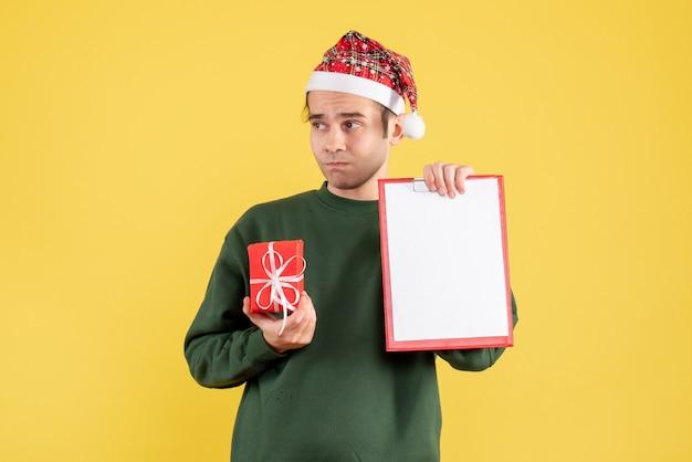 Вид спереди молодой человек с зеленым свитером, держащий подарок и буфер обмена, стоящий на желтом