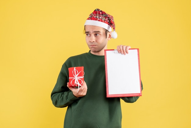 Giovane di vista frontale con regalo della tenuta del maglione verde e appunti che stanno sul colore giallo