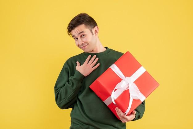 Вид спереди молодой человек с зеленым свитером, держащий подарок, положив руку на грудь на желтом