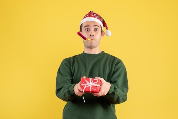 Вид спереди молодой человек с зеленым свитером, держащий подарок, используя шумогенератор, стоящий на желтом