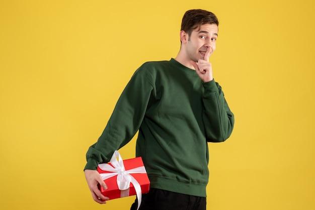 Giovane di vista frontale con il maglione verde che fa il segno di shh che sta sul colore giallo