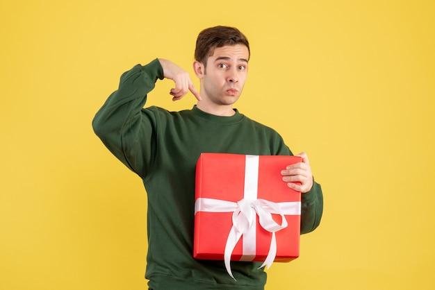 黄色の上に立っている緑のセーターと正面図の若い男
