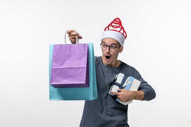 Vista frontale del giovane con i regali di festa sul muro bianco