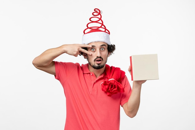 Front view of young man with holiday present on white wall