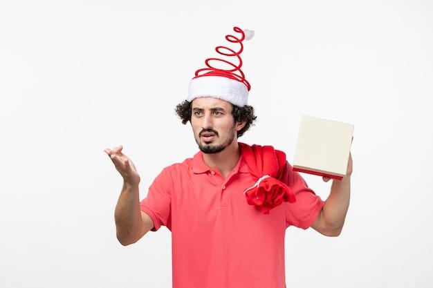 Vista frontale del giovane con regalo di festa sul muro bianco