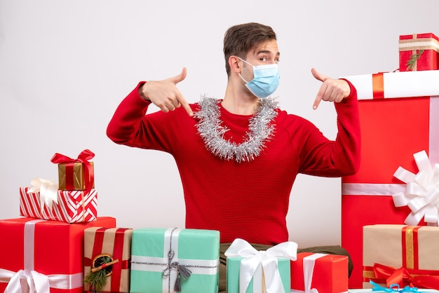 Front view young man with mask finger pointing himself sitting around xmas gifts
