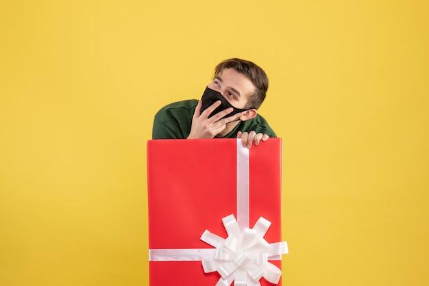 Вид спереди молодой человек с маской, прячущийся за большой подарочной коробкой на желтом
