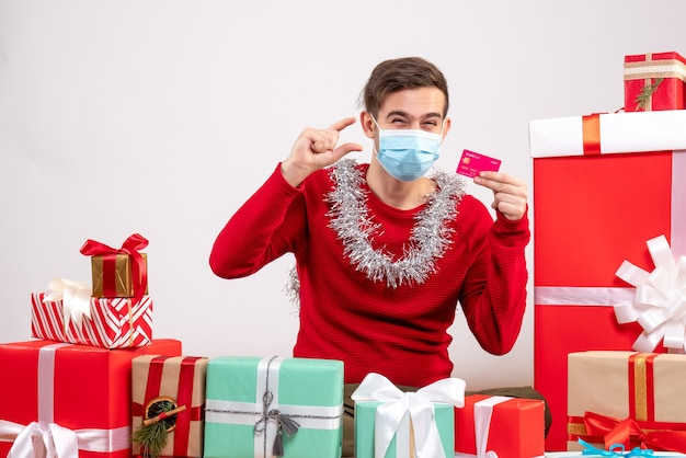 白のクリスマスプレゼントの周りに座っているカードを保持しているマスクを持つ正面図の若い男