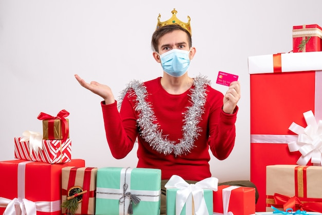 Front view young man with mask holding card sitting on floor xmas gifts