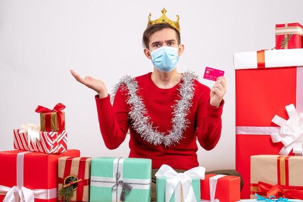 床に座っているカードを保持しているマスクを持つ正面図の若い男クリスマスプレゼント