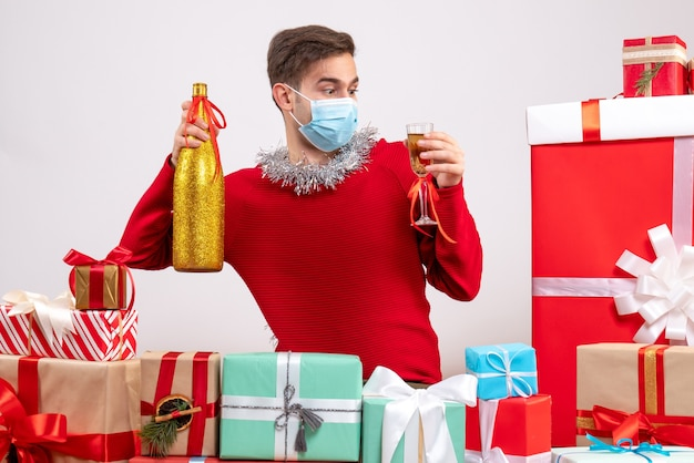 Front view young man with mask holding champagne around xmas gifts