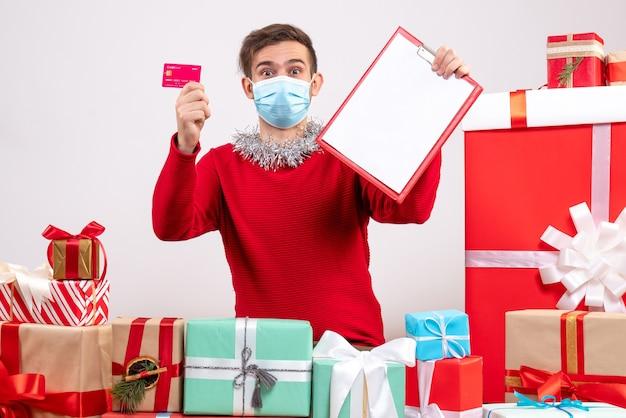 クリスマスプレゼントの周りに座っているクリップボードとカードを保持しているマスクを持つ正面図の若い男