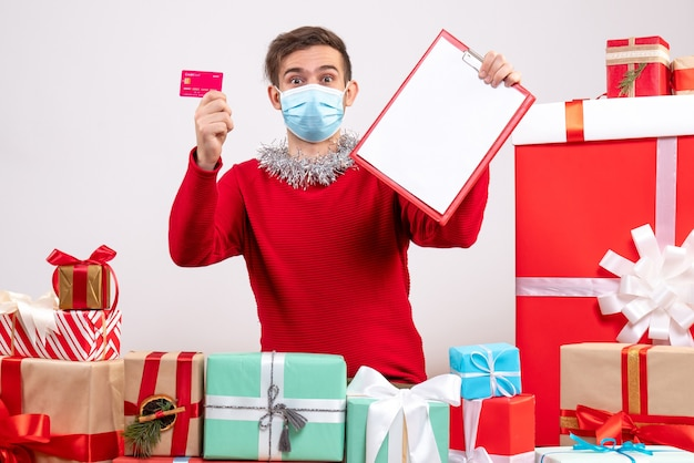 Front view young man with mask holding clipboard and card sitting around xmas gifts