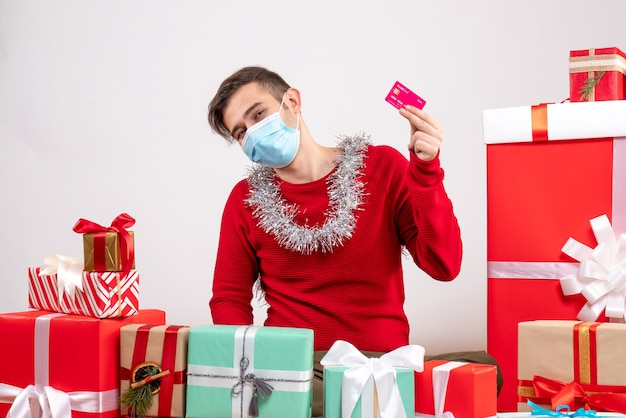 クリスマスプレゼントの周りにクレジットカードを保持しているマスクを持つ若い男の正面図