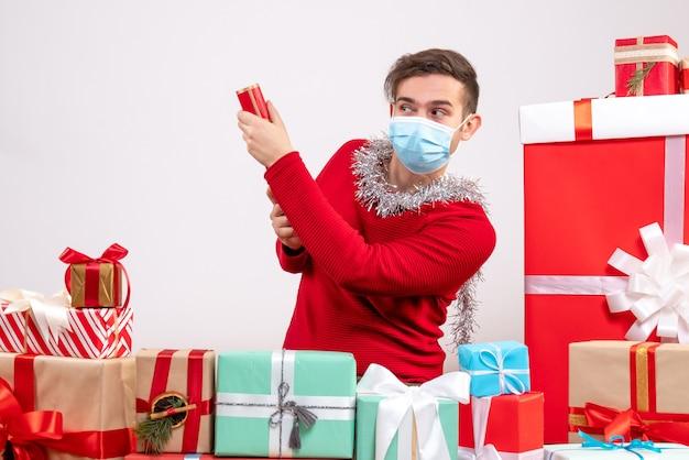 クリスマスプレゼントの周りに座っているパーティーポッパーを保持しているマスクを持つ正面図の若い男