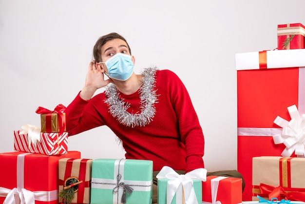 クリスマスプレゼントの周りに座って何かを聞いているマスクを持つ正面図の若い男