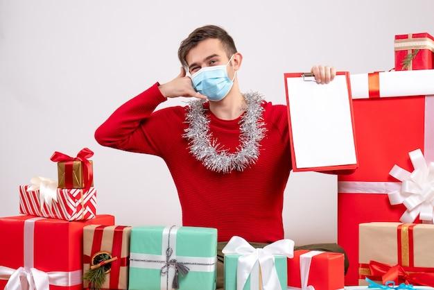 マスクをした正面図の若い男が床に座って電話ジェスチャーを電話してクリスマスプレゼント