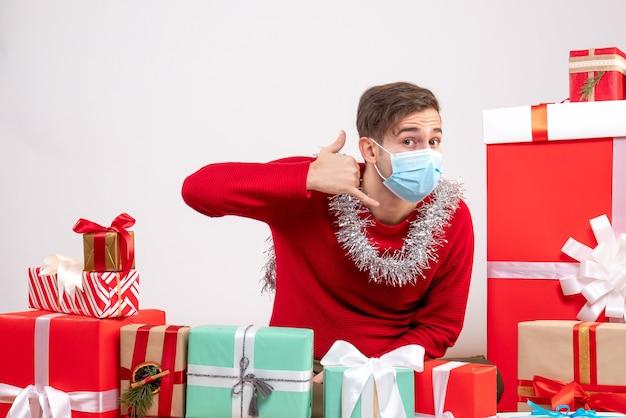 クリスマスプレゼントの周りに座って電話サインを作るマスクを持った正面図の若い男