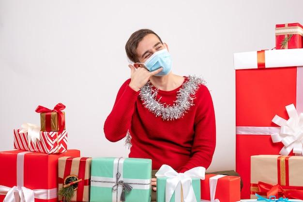 クリスマスプレゼントの周りに座って私にサインを呼んでマスクを作る正面図の若い男