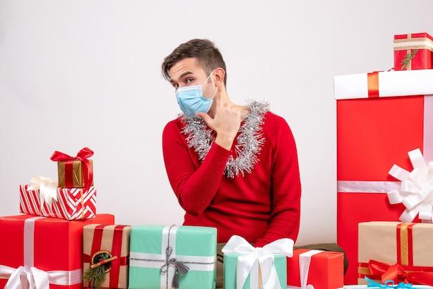 クリスマスプレゼントの周りに座って指銃を作るマスクと正面図