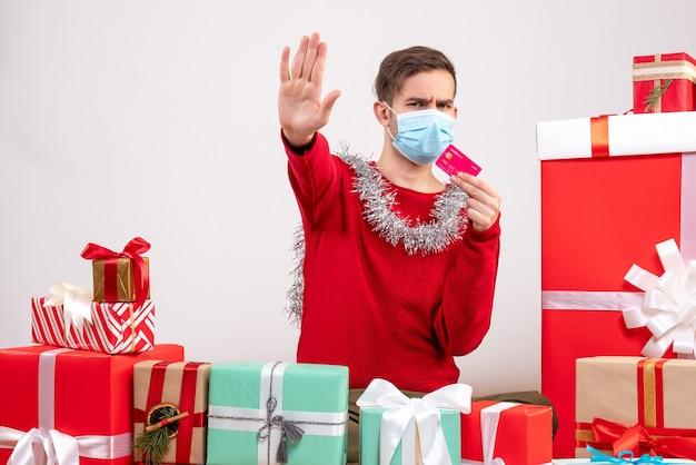 Вид спереди молодой человек с маской, делая знак остановки, сидя вокруг рождественских подарков