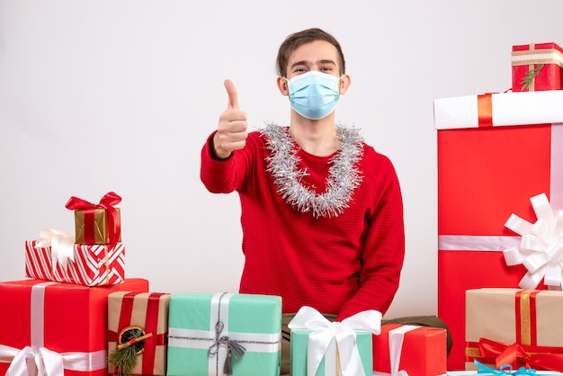 Front view young man with mask making thumb up sign sitting around xmas gifts