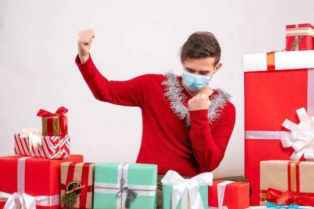 クリスマスプレゼントの周りに座って勝利のジェスチャーを作るマスクを持つ正面図の若い男