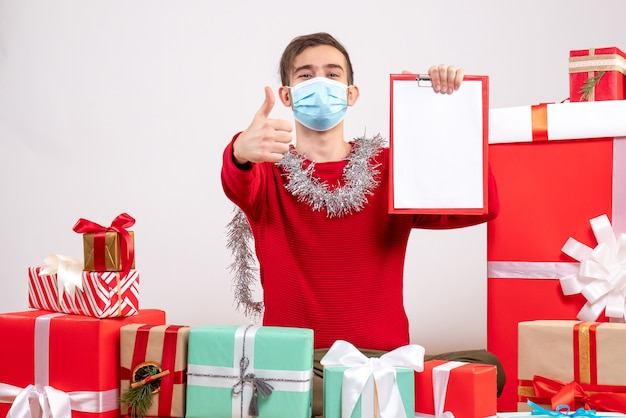 Front view young man with mask makng thumb up sign holding clipboard sitting around xmas gifts