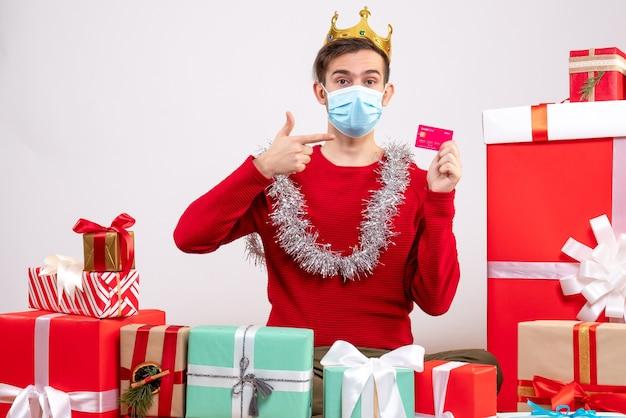 床に座っているカードを指しているマスクを持つ正面図の若い男クリスマスプレゼント