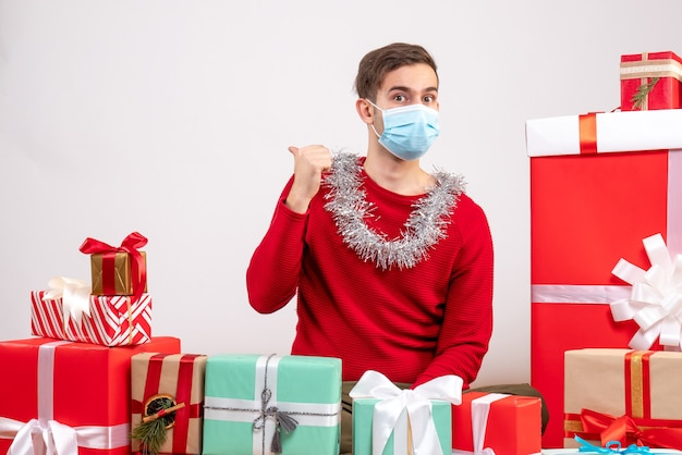 Front view young man with mask pointing at back sitting around xmas gifts on white